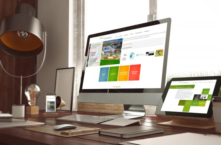 Startseite der Homepage des Rhön Gymnasiums auf drei Ausgabegeräten (Desktop, Laptop und Smartphone) Abgebildet ist die Hauptnavigation mit den aktuell wichtigsten Nachrichten und einem Slider.